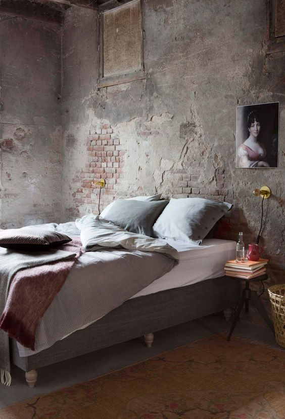 an industrial space with shabby chic brick walls, a grey upholstered bed, a refined artwork and a metal nightstand