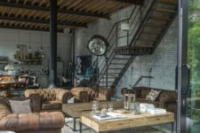 an industrial space with white brick walls, leather, wood and metal furniture, industrial lamps and a black fireplace