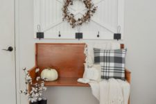an inviting farmhouse entryway with an amber stained wooden bench, a wooden rack, some decor and artworks