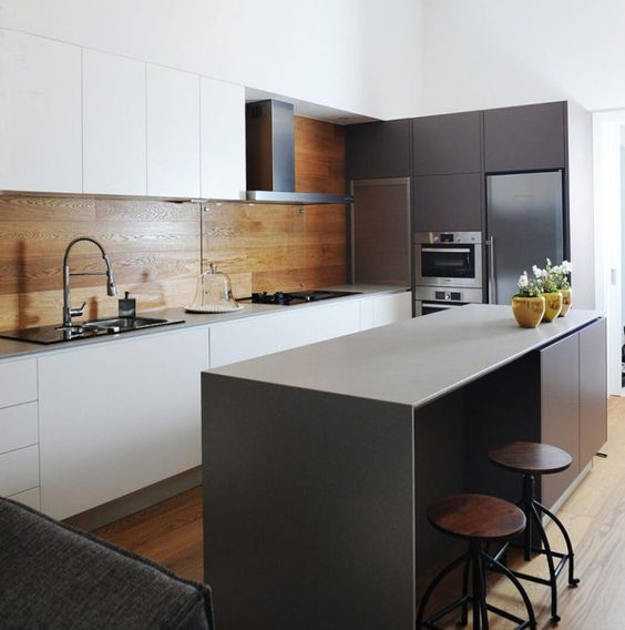 an ultra minimal kitchen in black and white, with a wooden backsplash for a touch of color and texture and to warm up the space