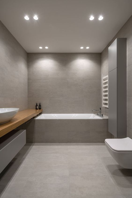 an ultra-minimalist grey bathroom with large scale tiles, built-in lights and a long wooden vanity