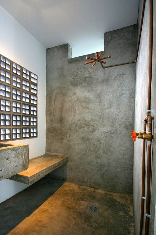 an ultra minimalist industrial bathroom with concrete walls and a floor, with concrete furniture and exposed pipes plus skylights
