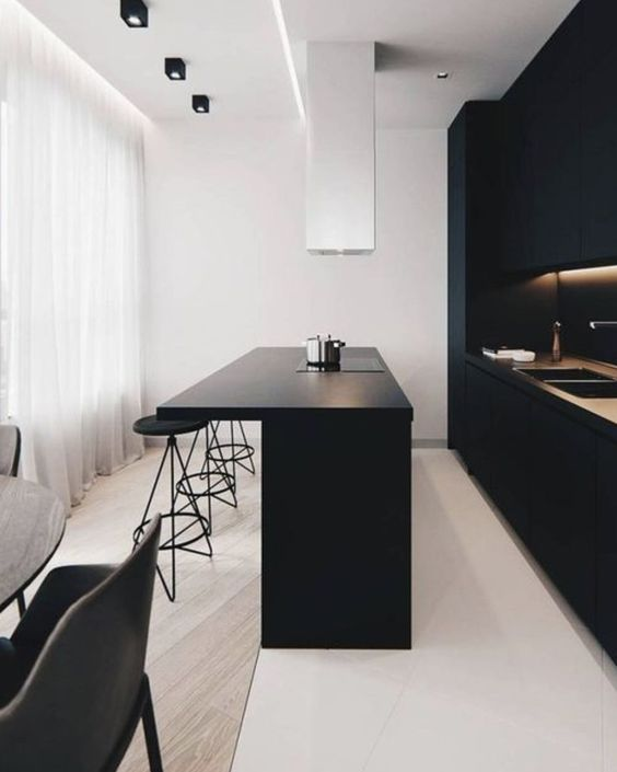 an ultra-minimalist kitchen with sleek black cabinets, built-in lights, a large kitchen island and a white hood