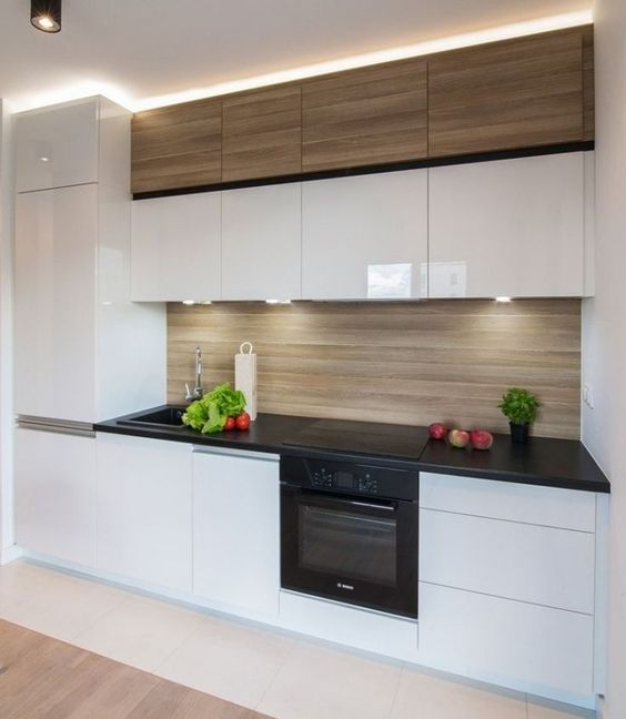 an ultra-minimalist white kitchen with a wooden backsplash and upper cabinets plus built-in lights is all about style