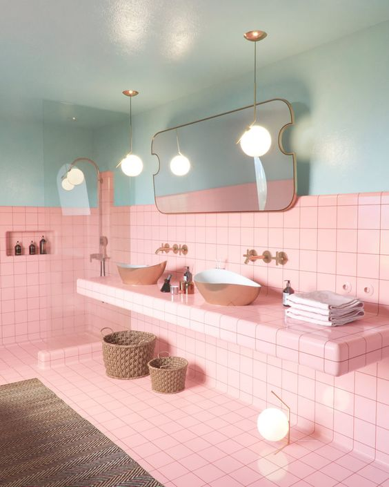 bright pink tiles paired with light blues, with gold fixtures and black grout for a bold look