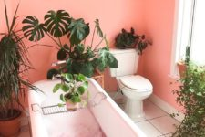 bright pink walls, potted greenery and white tiles on the floor are a recipe of a bold and cool bathroom
