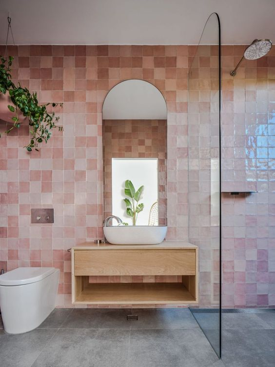 cool pink glazed tiles, white appliances and a floating wooden vanity plus some greenery