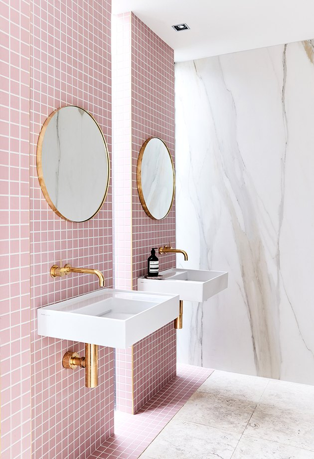 pink tiles and neutral marble slab walls plus gold fixtures make a cool contemporary bathroom with a touch of luxury