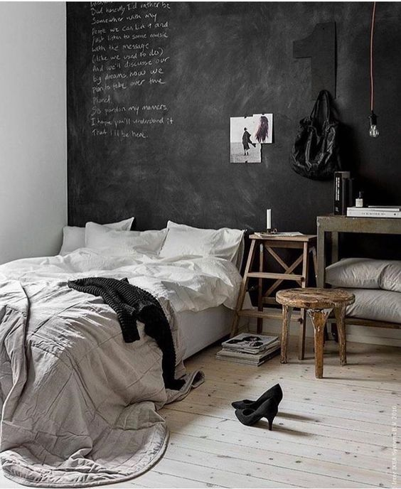 a chic bedroom in Nordic style, with rustic wooden furniture, an accent chalkboard wall and simple bedding
