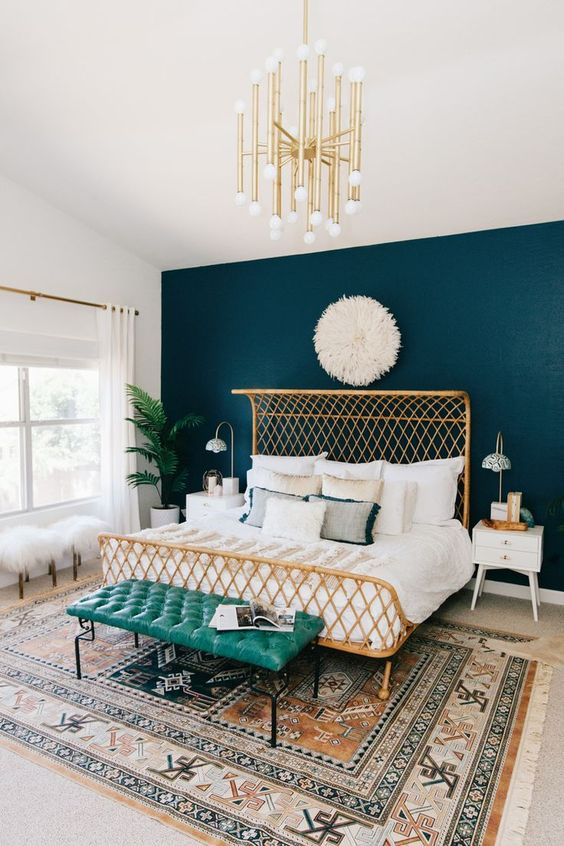a catchy boho bedroom with a wicker bed, a turquoise leather bench, a gold chandelier and faux fur stools