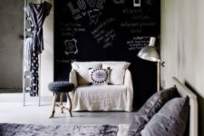 03 a chic bedroom with a chalkboard wall, neutral furniture, lots of concrete and laconic decor with touches of lilac