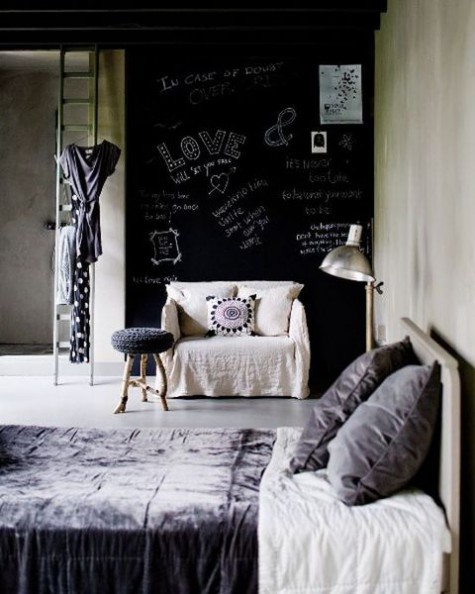 a chic bedroom with a chalkboard wall, neutral furniture, lots of concrete and laconic decor with touches of lilac