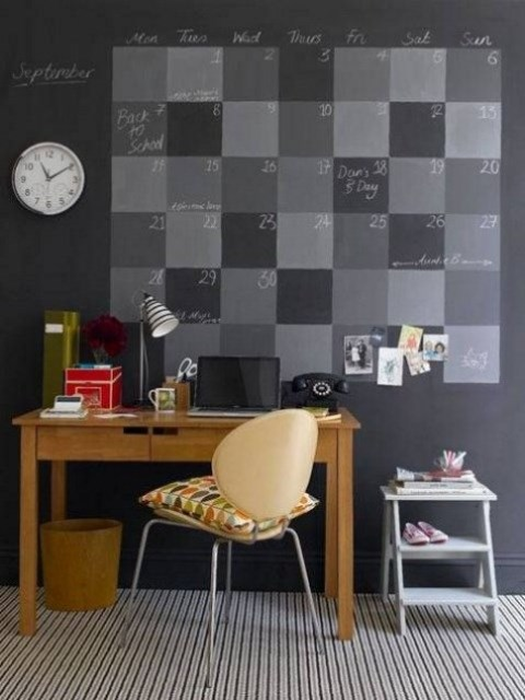 a stylish home office with a chalkboard accent wall with a large calendar suitable for each day of the month