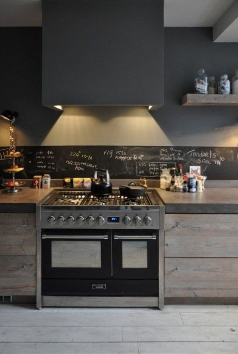 a stylish minimalist kitchen of wood and concrete, with a chalkboard backsplash and a large hood for an edgy look