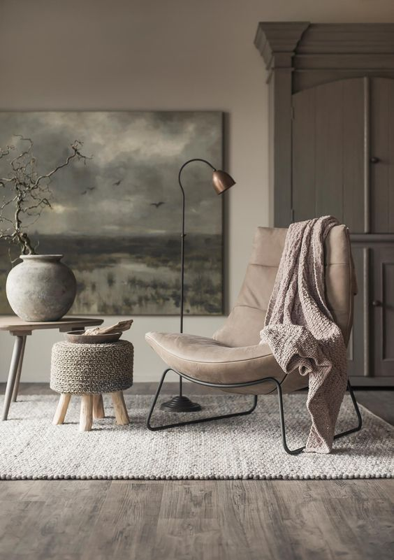 a chic and creative nook with a tan leather chair, a floor lamp, a crochet stool and a statement artwork