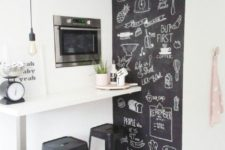 04 a small breakfast bar in the kitchen with built-in appliances and a chalkboard wall plus black stools looks stylish