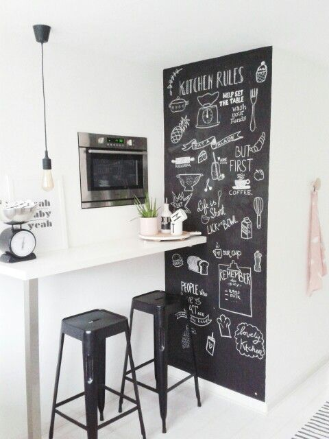 a small breakfast bar in the kitchen with built in appliances and a chalkboard wall plus black stools looks stylish