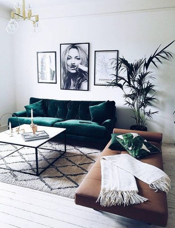 a chic contemporary living room in a monochromatic color scheme, with green velvet sofa and a wooden leather daybed