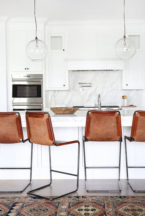 a chic neutral kitchen with brown leather stools that add texture and color to the space making it bolder