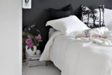 06 a small Nordic bedroom with a chalkboard wall and a white floor, black and white bedding, a stack of magazines as a nightstand