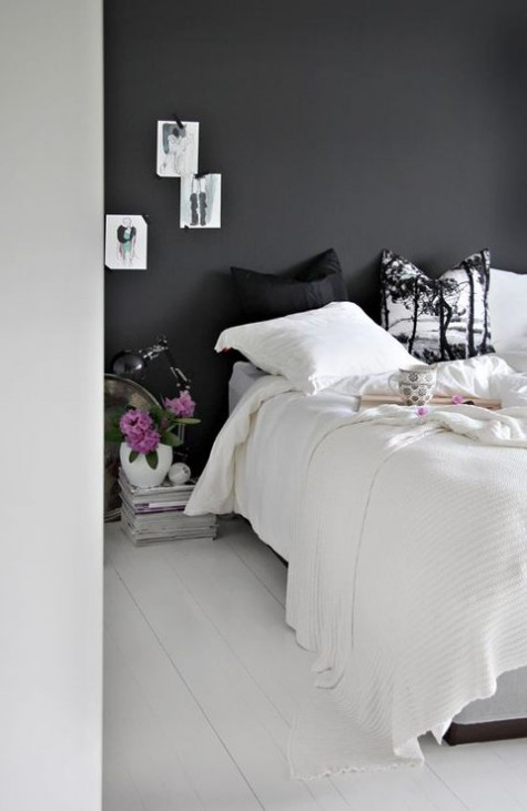 a small Nordic bedroom with a chalkboard wall and a white floor, black and white bedding, a stack of magazines as a nightstand
