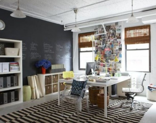 a monochromatic home office with a chalkboard wall that can be used for making notes and leaving messages