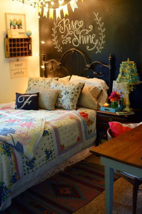 a small shabby chic bedroom with a chalkboard accent wall, lots of lights, colorful bedding, a bunting and rugs is very cozy