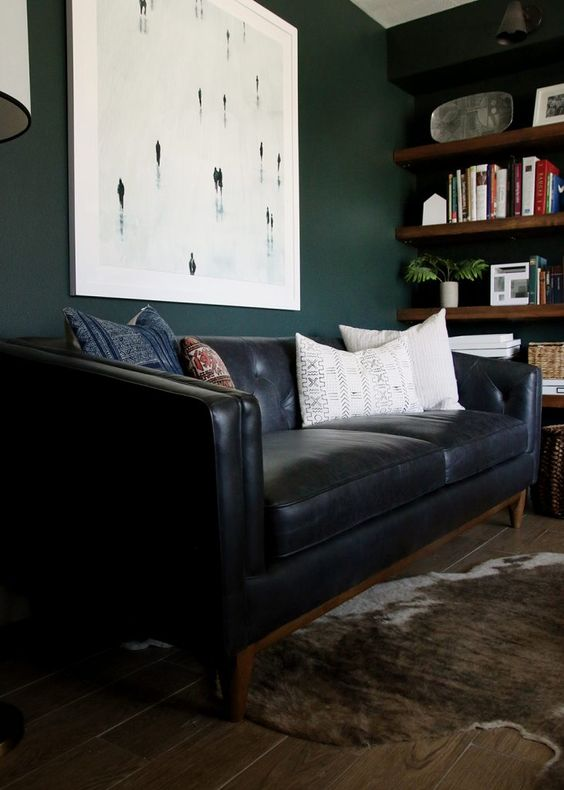 a moody home office with dark grene walls, a black leather sofa, a faux fur rug and stained wooden shelves