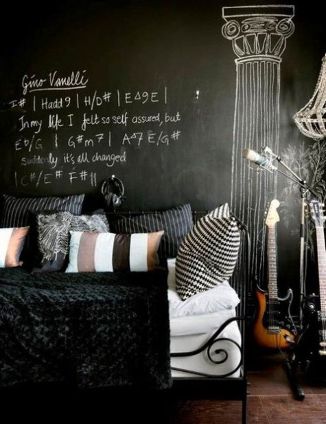an accent chalkboard wall matches the black forged bed and is used for formulas and necessary things not to forget