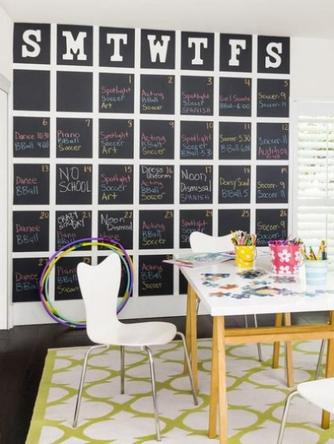 a bright home office with a large chalkboard calendar and colorful chalk to mark what to do