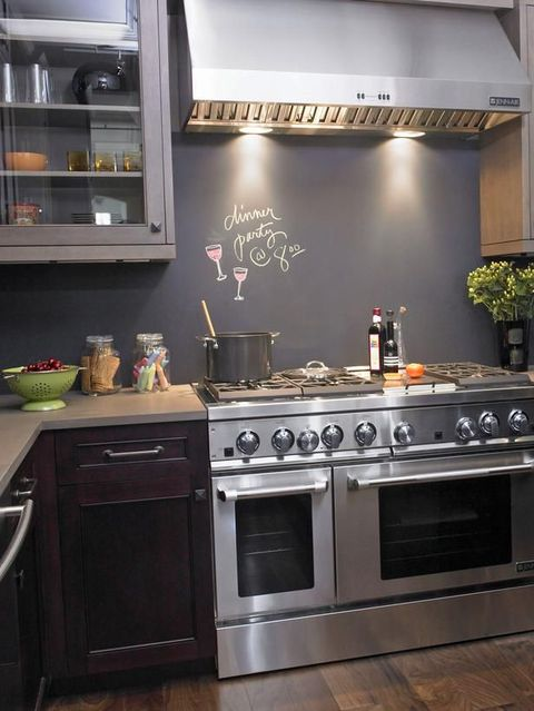 a dark modern kitchen with a chalkboard backsplash as a budget-friendly and cool idea to stand out