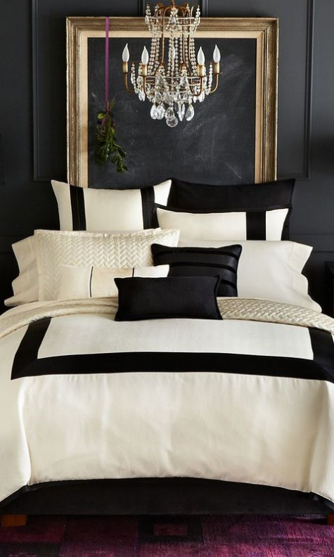 an elegant bedroom with a chalkboard wall, a gold refined frame, a crystal chandelier and black and white bedding