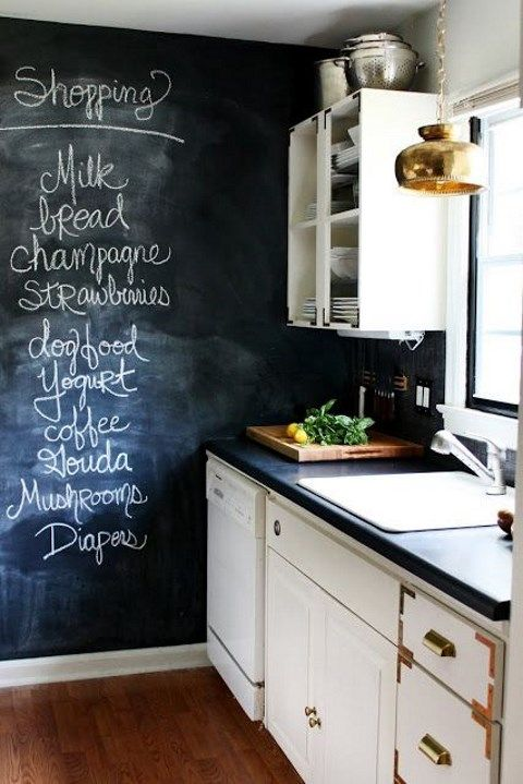 a monochromatic contrasting kitchen with a chalkboard wall and backsplash for noting food and drinks to buy