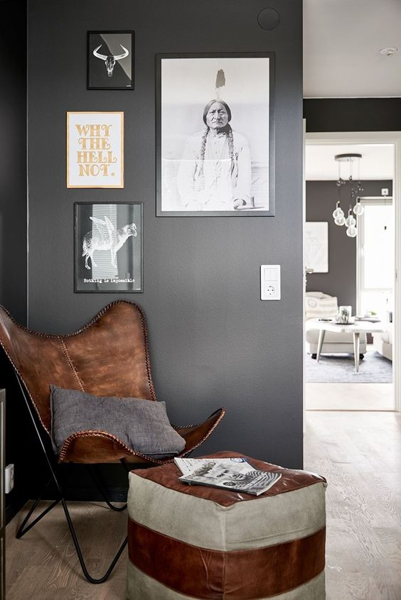 a creative reading nook with a gallery wall, a brown leather butterfly chair and a leather ottoman for a catchy look