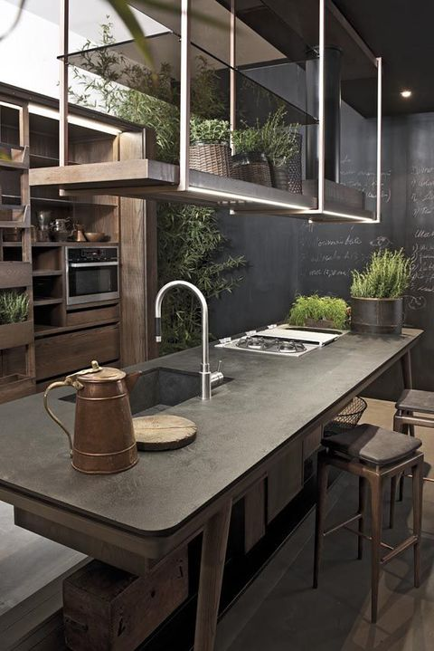 a large wood and metal industrial kitchen with a chalkboard wall with recipes is a cool space with much greenery