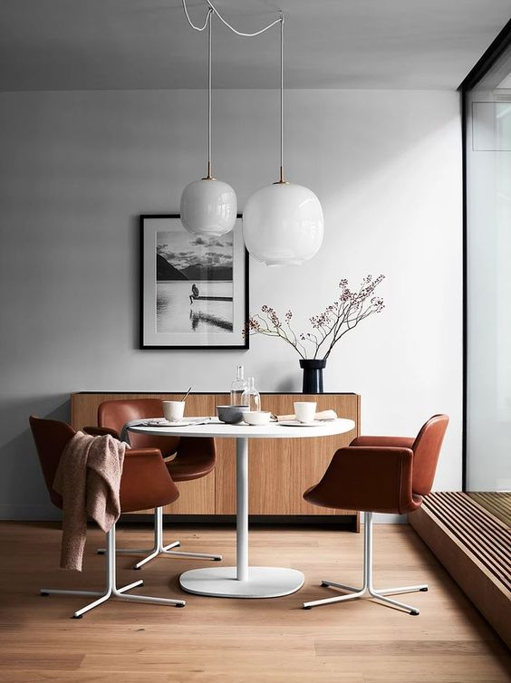 a cozy dining nook with a white table, brown leather chairs and a small sideboard by the window