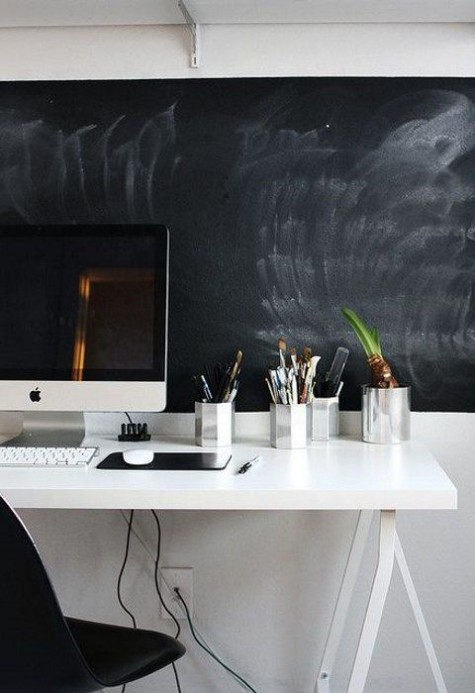 a monochromatic home office with a chalkboard wall for making marks and notes and to match the color scheme