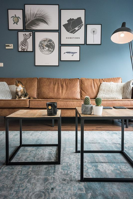 a welcoming living room with blue walls, a gallery wall, wooden tables and a sectional brown leather sofa