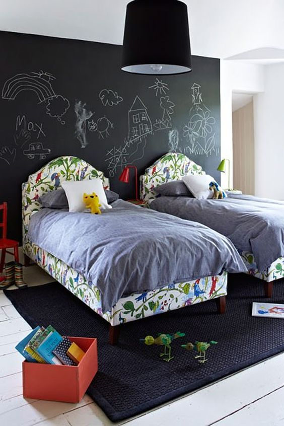a double kid bedroom with a chalkboard wall for art of all kinds, with colorful beds and furniture for a lively feel