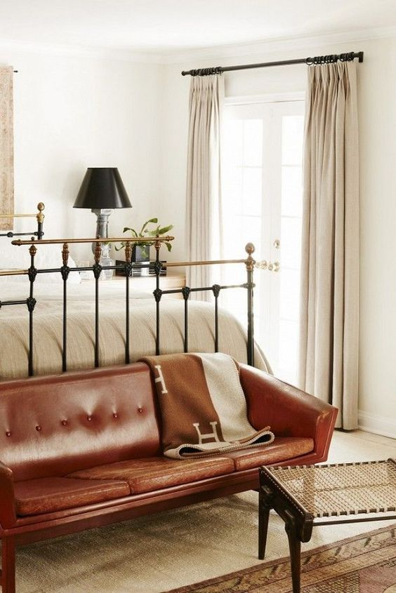 a vintage-inspired bedroom in neutrals, with a forged bed, a brown leather sofa and a woven footrest