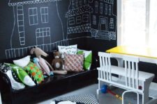 18 a bold modern kid's bedroom with chalkboard walls for art, with a black wooden bed and colorful pillows