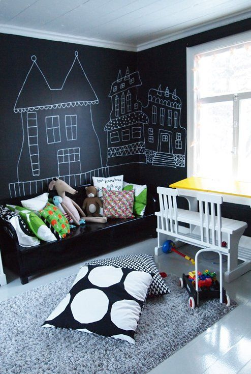 a bold modern kid's bedroom with chalkboard walls for art, with a black wooden bed and colorful pillows