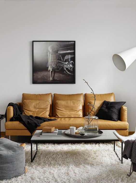 a stylish monochromatic living room in contemporary style, with a yellow leather sofa as a colorful statement