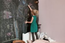 19 a kid bedroom done in light and light pink, with a black chalkboard wall for art, highly used by the owner