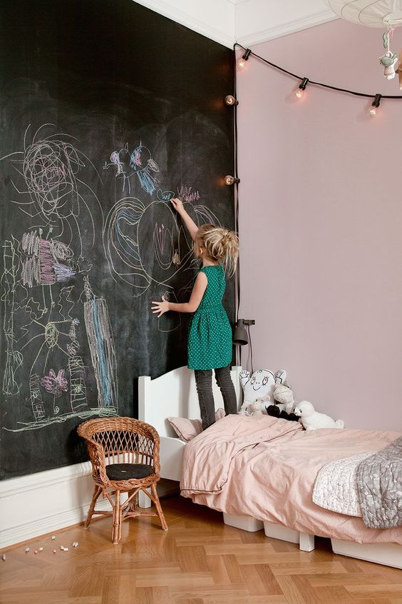 a kid bedroom done in light and light pink, with a black chalkboard wall for art, highly used by the owner