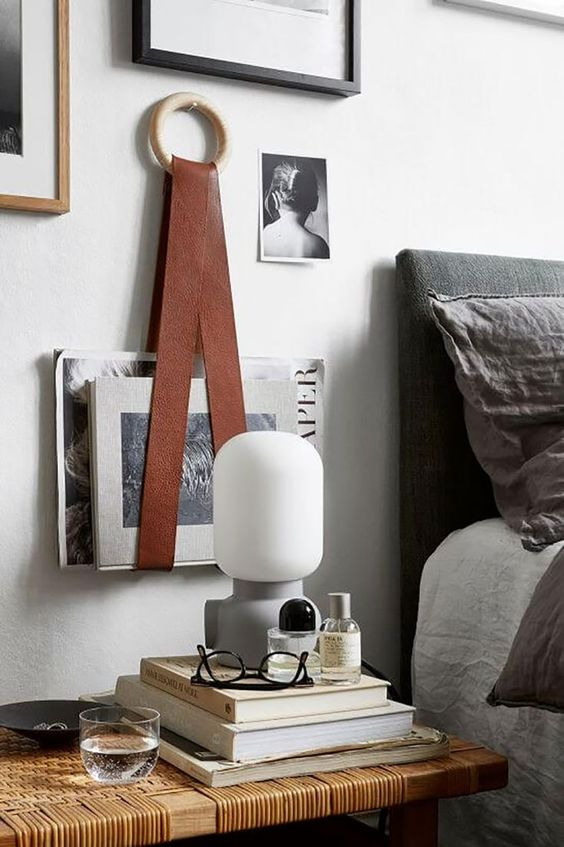 a book and magazine holder made of a wooden ring and leather straps is a creative idea for a chic bedroom