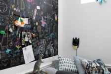 21 a modern kid's space with an accent chalkboard wall all chalked by the owner, some simple furniture and favorite toys