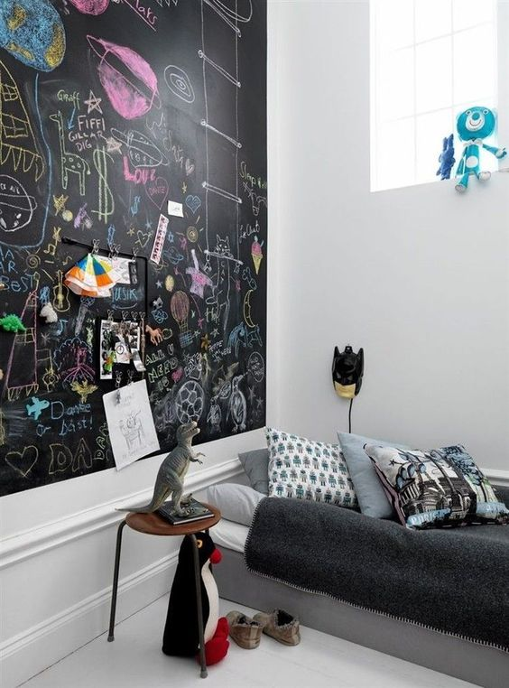 a modern kid's space with an accent chalkboard wall all chalked by the owner, some simple furniture and favorite toys