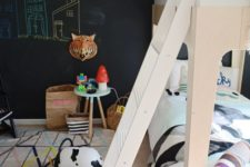 22 a Scandinavian kid's space with a chalkboard wall, simple wooden futniture, colorful touches for much fun