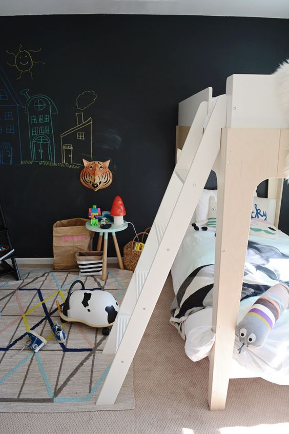 a Scandinavian kid's space with a chalkboard wall, simple wooden futniture, colorful touches for much fun